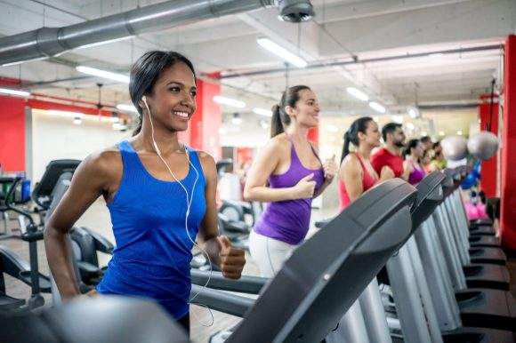 Happy group of people running on the treadmills at the gym and smiling – fitness concepts